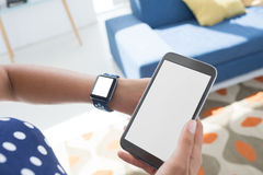 Θηλυκό εκτελεστικό κινητό τηλέφωνο εκμετάλλευσης και έλεγχος του χρόνου στο smartwatch στο γραφείο Στοκ Φωτογραφίες