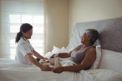 Θηλυκό εξυπηρετώντας πρόγευμα γιατρών στην ανώτερη γυναίκα στο κρεβάτι Στοκ φωτογραφίες με δικαίωμα ελεύθερης χρήσης
