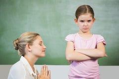 Θηλυκό ζητώντας συγγνώμη κορίτσι δασκάλων στην τάξη Στοκ Εικόνες