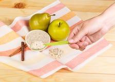 Θηλυκό κουτάλι χεριών με το κουάκερ και φρούτα στο ελαφρύ ξύλο Στοκ φωτογραφίες με δικαίωμα ελεύθερης χρήσης