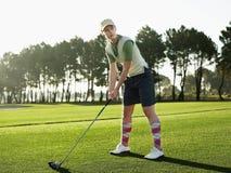 Θηλυκό να τοποθετήσει στο σημείο αφετηρίας παικτών γκολφ μακριά στο γήπεδο του γκολφ Στοκ εικόνα με δικαίωμα ελεύθερης χρήσης