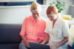 Θηλυκό νοσοκόμα και ανώτερη γυναίκα που χρησιμοποιεί το lap-top Στοκ φωτογραφίες με δικαίωμα ελεύθερης χρήσης