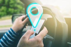 Θηλυκό οδηγώντας αυτοκίνητο και χρησιμοποίηση της ναυσιπλοΐας app ΠΣΤ στο smartphone Στοκ Εικόνες