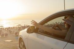 Θηλυκό που απολαμβάνει το ηλιοβασίλεμα από το αυτοκίνητο στο χώρο στάθμευσης παραλιών Στοκ φωτογραφία με δικαίωμα ελεύθερης χρήσης