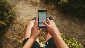Θηλυκό που ελέγχει την περίληψη του τρεξίματός της στο κινητό τηλέφωνο Στοκ Εικόνα
