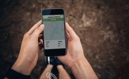Θηλυκό που ελέγχει την περίληψη του τρεξίματός της στο κινητό τηλέφωνο Στοκ εικόνα με δικαίωμα ελεύθερης χρήσης