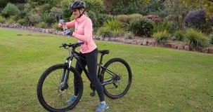 Θηλυκό πόσιμο νερό ποδηλατών στο πάρκο απόθεμα βίντεο