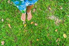 Θηλυκό πόδι στα σανδάλια σε μια πράσινη χλόη Στοκ Φωτογραφία