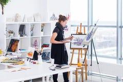 Θηλυκό σχέδιο ζωγράφων στο στούντιο τέχνης που χρησιμοποιεί easel Πορτρέτο μιας νέας γυναίκας που χρωματίζει με τα χρώματα ακουαρ στοκ φωτογραφία με δικαίωμα ελεύθερης χρήσης