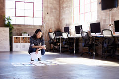 Θηλυκό σχεδιάγραμμα προγραμματισμού σχεδιαστών στο πάτωμα του σύγχρονου γραφείου στοκ φωτογραφία