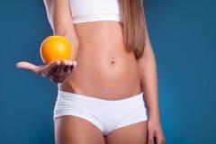 Θηλυκό σώμα ομορφιάς με το πορτοκάλι υγιής τρόπος ζωής έννοιας Στοκ Εικόνες