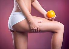 Θηλυκό σώμα ομορφιάς με το πορτοκάλι υγιής τρόπος ζωής έννοιας Στοκ Εικόνα