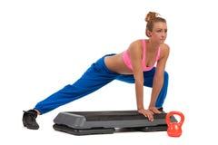 Θηλυκό τέντωμα στο αεροβικό βήμα πριν από Workout στοκ εικόνα