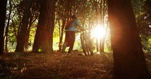 Θηλυκό τρέξιμο βουνών που περπατά με το ποδήλατο απόθεμα βίντεο