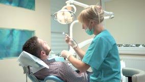 Θηλυκό τρυπώντας με τρυπάνι δόντι οδοντιάτρων του ασθενή στην οδοντική κλινική απόθεμα βίντεο