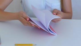 Θηλυκό φύλλο χεριών σπουδαστών copybook στην άσπρη έννοια εκπαίδευσης δωματίων απόθεμα βίντεο
