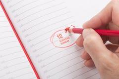Θηλυκό χέρι με ένα κόκκινο μολύβι Στοκ εικόνα με δικαίωμα ελεύθερης χρήσης