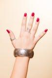 Θηλυκό χέρι με το μανικιούρ και armlet Στοκ Εικόνες