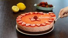 Θηλυκό χέρι με το φτυάρι που παίρνει το κομμάτι του φρέσκου κέικ με τις φράουλες απόθεμα βίντεο