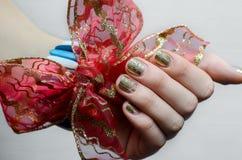 Θηλυκό χέρι με το χρυσό σχέδιο καρφιών και το κόκκινο τόξο Στοκ εικόνες με δικαίωμα ελεύθερης χρήσης