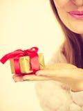 Θηλυκό χέρι με το χρυσό δώρο κιβωτίων Στοκ Εικόνες