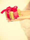 Θηλυκό χέρι με το χρυσό δώρο κιβωτίων Στοκ φωτογραφία με δικαίωμα ελεύθερης χρήσης