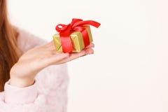 Θηλυκό χέρι με το χρυσό δώρο κιβωτίων Στοκ εικόνες με δικαίωμα ελεύθερης χρήσης