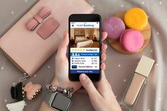 Θηλυκό χέρι με app εκμετάλλευσης ρολογιών κοσμήματος τηλεφωνικό την κράτηση ξενοδοχείων Στοκ Εικόνες