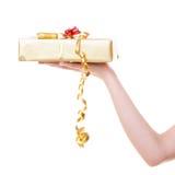 Θηλυκό χέρι που δίνει στα Χριστούγεννα το χρυσό κιβώτιο δώρων με την κορδέλλα. Διακοπές. Στοκ φωτογραφία με δικαίωμα ελεύθερης χρήσης