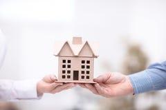Θηλυκό χέρι που δίνει τα κλειδιά από το νέο διαμέρισμα στο αρσενικό χέρι στο υπόβαθρο Στοκ Φωτογραφίες