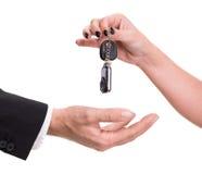 Θηλυκό χέρι που δίνει το κλειδί αυτοκινήτων στο αρσενικό χέρι Στοκ Φωτογραφίες