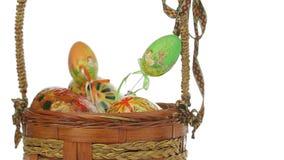Θηλυκό χέρι που βάζει τα αυγά Πάσχας στο καλάθι απόθεμα βίντεο