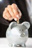 Θηλυκό χέρι που βάζει το νόμισμα στη piggy τράπεζα στοκ φωτογραφίες