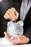 Θηλυκό χέρι που βάζει το νόμισμα στη piggy τράπεζα στοκ εικόνες με δικαίωμα ελεύθερης χρήσης