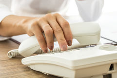 Θηλυκό χέρι που κρατά ένα άσπρα τηλεφωνικά μικροτηλέφωνο και ένα diali γραμμών εδάφους Στοκ Φωτογραφία