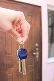 Θηλυκό χέρι που κρατά ένα κλειδί στο υπόβαθρο των πορτών στοκ φωτογραφίες
