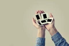 Θηλυκό χέρι που κρατά ένα παλαιό πλαίσιο φωτογραφικών διαφανειών φωτογραφιών Εκλεκτής ποιότητας κοιτάξτε στοκ εικόνες