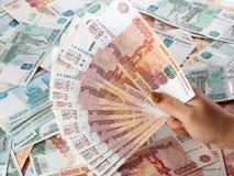 Θηλυκό χέρι που κρατά ένα ρωσικό ρούβλι χρημάτων μεγάλου ποσού Στοκ Φωτογραφία