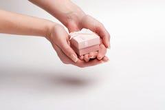 Θηλυκό χέρι που κρατά ένα δώρο με ένα τόξο Στοκ εικόνα με δικαίωμα ελεύθερης χρήσης