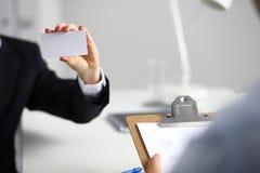 Θηλυκό χέρι που κρατά μια κενή συνεδρίαση επαγγελματικών καρτών στο γραφείο, εκλεκτική εστίαση Στοκ εικόνες με δικαίωμα ελεύθερης χρήσης