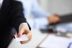 Θηλυκό χέρι που κρατά μια κενή συνεδρίαση επαγγελματικών καρτών στο γραφείο, εκλεκτική εστίαση Στοκ φωτογραφία με δικαίωμα ελεύθερης χρήσης