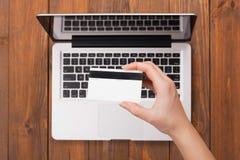 Θηλυκό χέρι που κρατά μια πληρωμή καρτών σε ένα lap-top Στοκ φωτογραφία με δικαίωμα ελεύθερης χρήσης