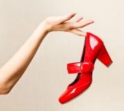 Θηλυκό χέρι που κρατά τα κόκκινα παπούτσια βερνικιών σε ένα υψηλό τακούνι. στοκ εικόνες