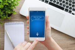 Θηλυκό χέρι που κρατά το άσπρο τηλέφωνο με app τον προσωπικό βοηθό scre Στοκ Εικόνες