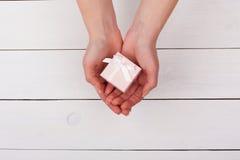 Θηλυκό χέρι που κρατά το ρόδινο δώρο στα χέρια σε έναν άσπρο ξύλινο πίνακα Στοκ Εικόνα