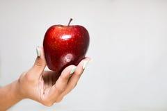 Θηλυκό χέρι που προσφέρει ένα κόκκινο μήλο Στοκ Εικόνες