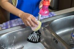 Θηλυκό χέρι που πλένει το παν βατραχοπέδιλο με το σφουγγάρι στοκ φωτογραφίες με δικαίωμα ελεύθερης χρήσης