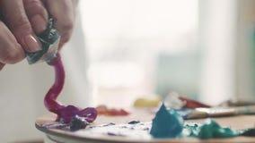 Θηλυκό χέρι που συμπιέζει το χρώμα επάνω σε μια παλέτα κοντά επάνω απόθεμα βίντεο