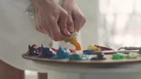 Θηλυκό χέρι που συμπιέζει το χρώμα στην παλέτα, κινηματογράφηση σε πρώτο πλάνο φιλμ μικρού μήκους
