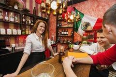 Θηλυκό bartender με τους αρσενικούς πελάτες στο μετρητή φραγμών Στοκ φωτογραφία με δικαίωμα ελεύθερης χρήσης